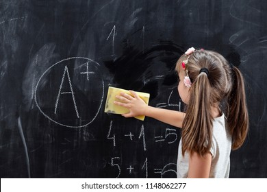 Schoolgirl wiping blackboard with a sponge after solving math problems and getting an A in math. Focus on the sponge and the hand