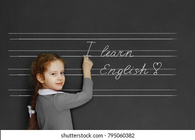 "Schoolgirl writes: ""I learn English!"" on blackboard. Education concept."