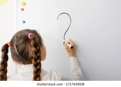 Schoolgirl writing big question mark on the blackboard. Concept of difficult question, curiosity, studying, developing, asking questions