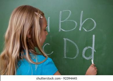 Schoolgirl writing letters on a blackboard