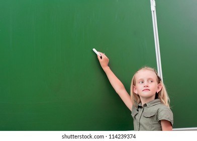 Schoolgirl writing on the blackboard, the beginning of the new academic year