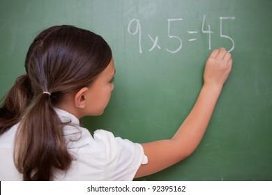 Schoolgirl writing a result on a blackboard
