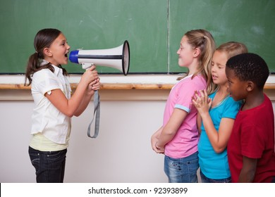 Schoolgirl yelling through a megaphone to her classmates in a classroom
