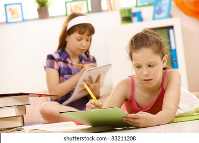 Schoolgirls doing homework at home, writing into exercise books.?