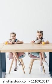 schoolgirls eating cereals for breakfast together on white
