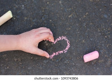 Schoolgirls hand shows heart gesture on chalk drawing