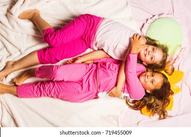 Schoolgirls have pajama party with funny pillows. Kids in pink pajamas have fun. Children with smiling faces lie on light pink blanket background and hug. Childhood, party and happiness concept.
