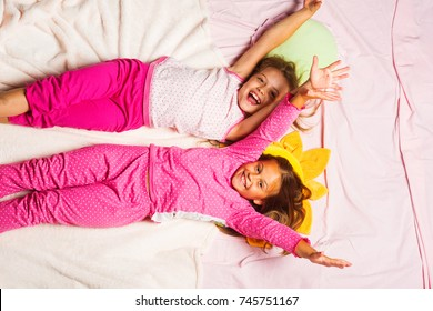 Schoolgirls have pajama party with funny pillows. Children with smiling faces lie on light pink blanket background and hold hands up. Kids in pink pajamas, top view. Childhood and happiness concept.