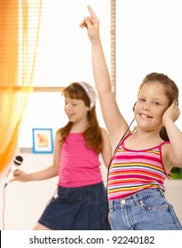Schoolgirls having fun with headset and microphone, dancing at home.?