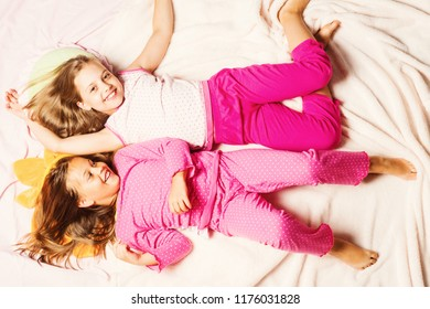 Schoolgirls having pajama party. Children with smiling faces lie on light pink blanket background, top view. Kids in pink polka dotted pajamas have fun. Childhood, party and happiness concept.
