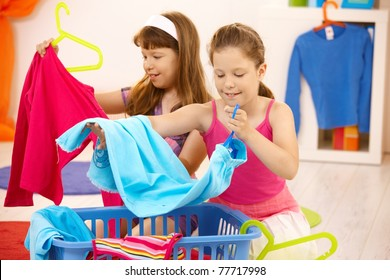 Schoolgirls helping with housework, putting clothes away, smiling.?