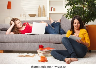 Schoolgirls learning together in living room with books and computer.