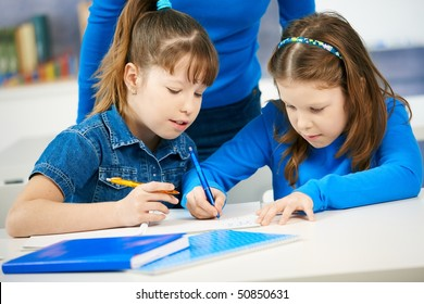Schoolgirls learning together in primary school classroom. Elementary age children.