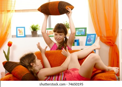 Schoolgirls playing pillow fight on sofa in living room.?