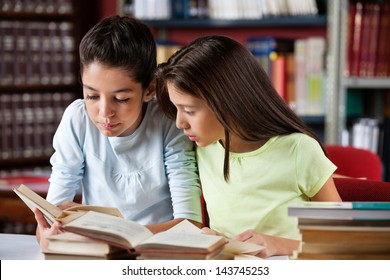 Schoolgirls reading book together while sitting at table in library