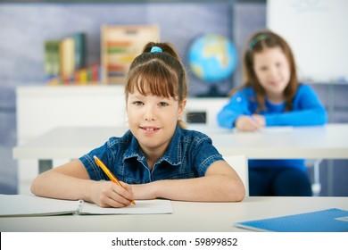 Schoolgirls sitting at desk in primary school classroom. Elementary age children.?