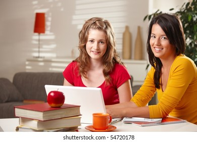 Schoolgirls sitting at table at home with exercise book and laptop smiling at camera.