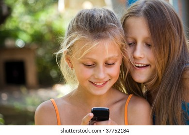 schoolgirls in summer park. Two girlfriends consider the message on a mobile phone
