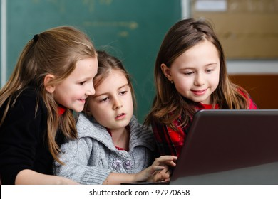 Schoolgirls working with laptop in classroom