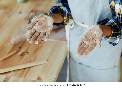 Schoolkid in apron showing his dirty palms after work with clay at handcraft lesson