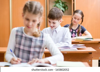 schoolkids work at lesson in classroom