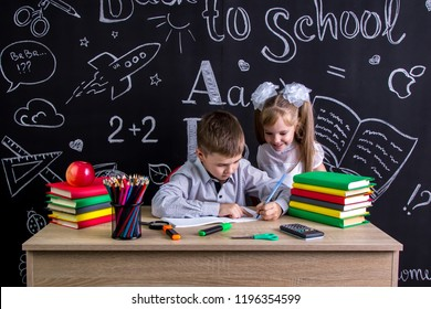 Schoolkids working at the desk with books, school supplies. Left-handed boy writing the text and smiling girl looking at the process.