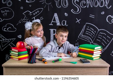 Schoolkids working at the desk with books, school supplies. Left-handed boy writing the text and smiling girl standing near him, both looking straight to the camera.