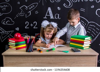 Schoolkids working at the desk with books, school supplies. Right-handed girl writing the text on the exercise book and serious boy pointing her the text, pupils in the deep process of studying.