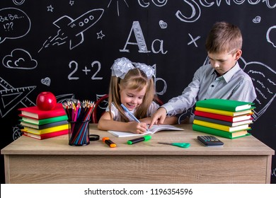 Schoolkids working at the desk. Right-handed smiling girl writing the text on the exercise book and serious boy pointing her the text, pupils in the deep process of studying.