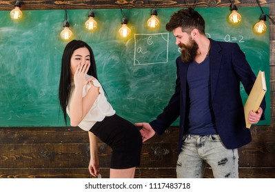 Schoolmaster punishes sexy student with slapping on her buttocks. Man with beard slapping sexy student, chalkboard on background. Girl on guilty and helpless face punished by teacher. Sex game concept