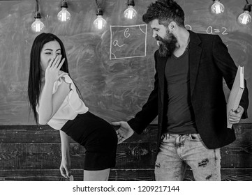 Schoolmaster punishes sexy student with slapping on her buttocks. Girl on guilty and helpless face punished by teacher. Man with beard slapping sexy student, chalkboard on background. Sex game concept