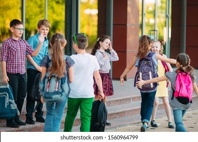 Schoolmates go to school. Students greet each other