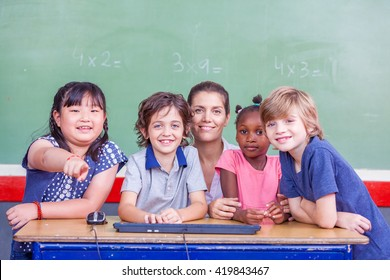 Schoolmates and teacher together smiling in classroom.