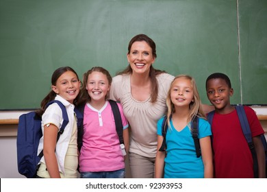 Schoolteacher posing with her pupils in a classroom