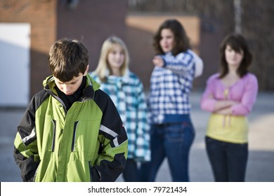 Schoolyard bullies, boy walks away with head down