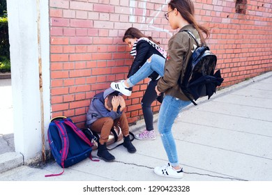 Schoolyard bullies, concept of this taking place after school,Aggressive teenagers bullying boy outdoors. - Image