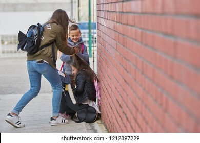Schoolyard bullies, later afternoon signified by the long shadows, concept of this taking place after school,Aggressive teenagers bullying boy outdoors.