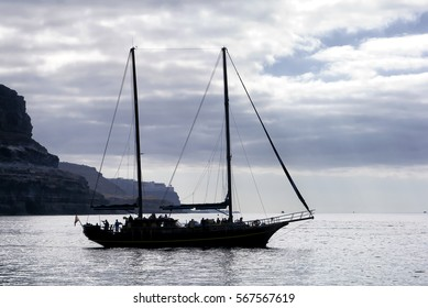Schooner leaving port; schooner silhouetted against evening sky