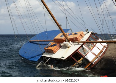 A schooner listing to its side and slowly sinking