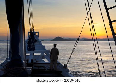 Schooner Sunrise. A traditional Indonesian schooner, called a Phinisi schooner, travels through the Indonesian archipelago near the island of Komodo during a beautiful sunrise.