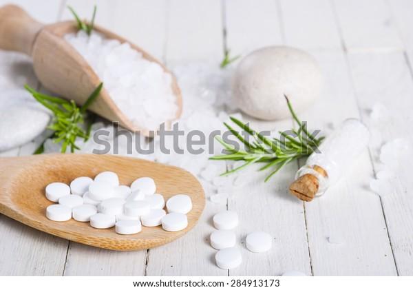 Schuessler salts and salt crystal on white wood table