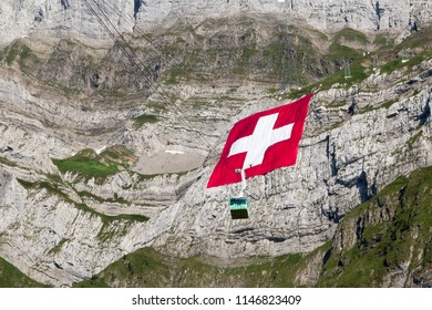 Schwaegalp, Switzerland: 31.07.2018 - Huge Swiss national flag (80mx80m, which is the biggest Swiss flag in the world) hangs on the Saentis mountain on National Day