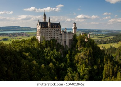 Schwangau, Bavaria, Germany - June 15 2014 : View of the Schloss Neuschwanstein castle, home of King Ludwig II, high on a densely forested hill with the Alpsee Lake in the background