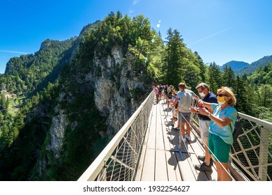 Schwangau, Germany - July 8th 2020: Tourists at the Marienbrücke (Mary's Bridge), a pedestrian bridge allowing a stunning view of Neuschwanstein Castle, near Füssen, Bavaria, Germany