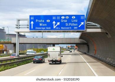 SCHWECHAT, AUSTRIA - July 17, 2012: Road with cars and signpos to Vienna, Prague, Gratz, Lenses near Vienna-Schwechat International Airport.