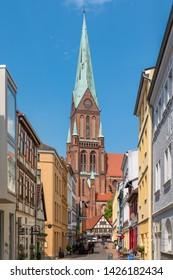 Schwerin, Germany - June 5, 2019: The Schwerin Cathedral (German: Schweriner Dom) with downtown street.