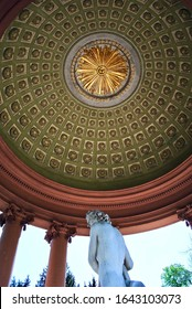 Schwetzingen, Germany - 2015: Schloss Schwetzingen, a schloss or palace in Baden-Württemberg. The Apollo temple with a green and gold domed ceiling. Apollo statue with sunburst ceiling medallion.
