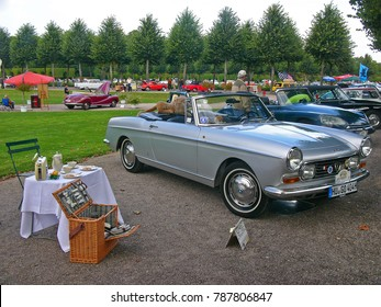 SCHWETZINGEN, GERMANY, SEPTEMBER 1, 2007. Classic car Peugeot 404 cabriolet Pininfarina, built in France in 1967 and a picnic set as decor, photographed at a car event in Germany
