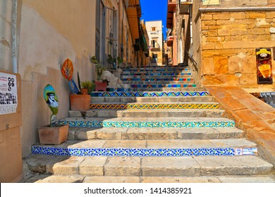 Sciacca, Agrigento, Sicily, Italy 26.08.2018. Cityscape with old historical buildings, narrow street and medieval steps with colorful ceramic decorations