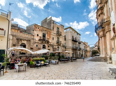 SCICLI, ITALY - SEPTEMBER 22, 2017 - People enjoying a cocktail in front of the baroque Church of San Giovanni Evangelista in Scicli, Ragusa - Sicily (Italy)